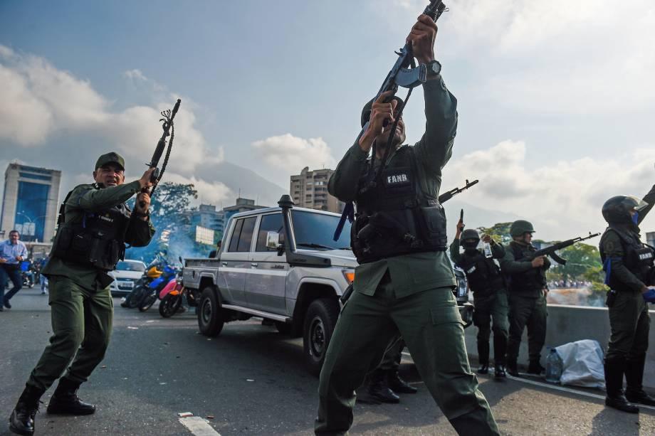 Membros da Guarda Nacional Bolivariana que se juntaram ao líder de oposição venezuelana e autoproclamado presidente em exercício Juan Guaidó disparam para o ar para repelir as forças leais ao presidente Nicolás Maduro perto da base militar de 'La Carlota' em Caracas - 30/04/2019