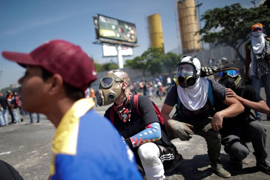 Manifestantes de oposição usam máscaras de gás para se proteger dos ataques das forças leais a Nicolás Maduro durante confrontos nos arredores da base aérea La Carlota em Caracas, na Venezuela - 30/04/2019