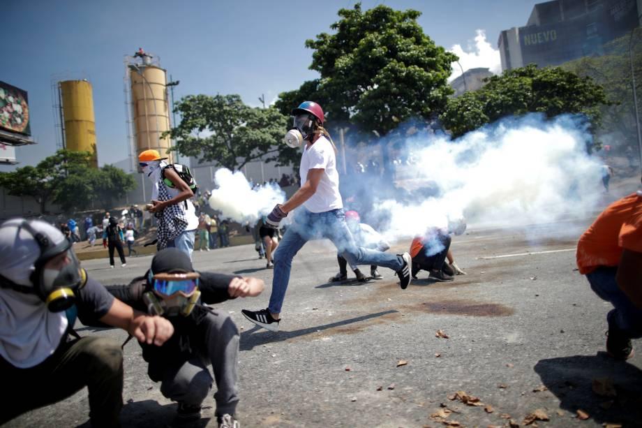 Manifestantes de oposição se protegem de gás lacrimogêneo em uma rua perto da Base Aérea Generalíssimo Francisco de Miranda La Carlota em Caracas durante confronto com forças leais ao presidente Nicolás Maduro - 30/04/2019