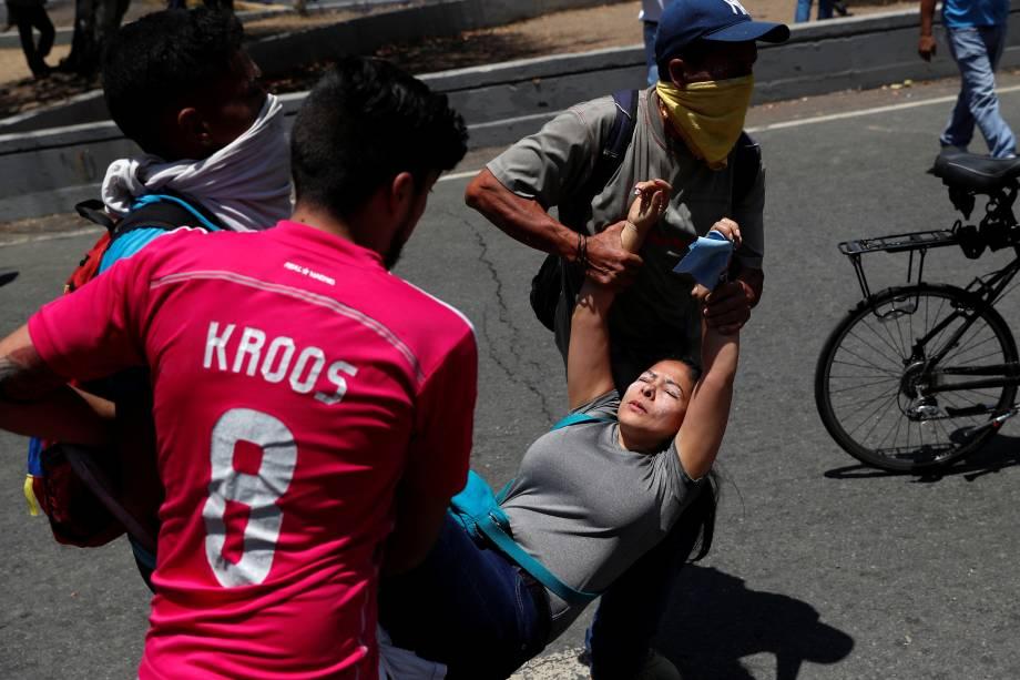 Manifestantes carregam uma mulher ferida durante confrontos com forças leais a Nicolás Maduro nos arredores da base aérea de La Carlota em Caracas, na Venezuela - 30/04/2019