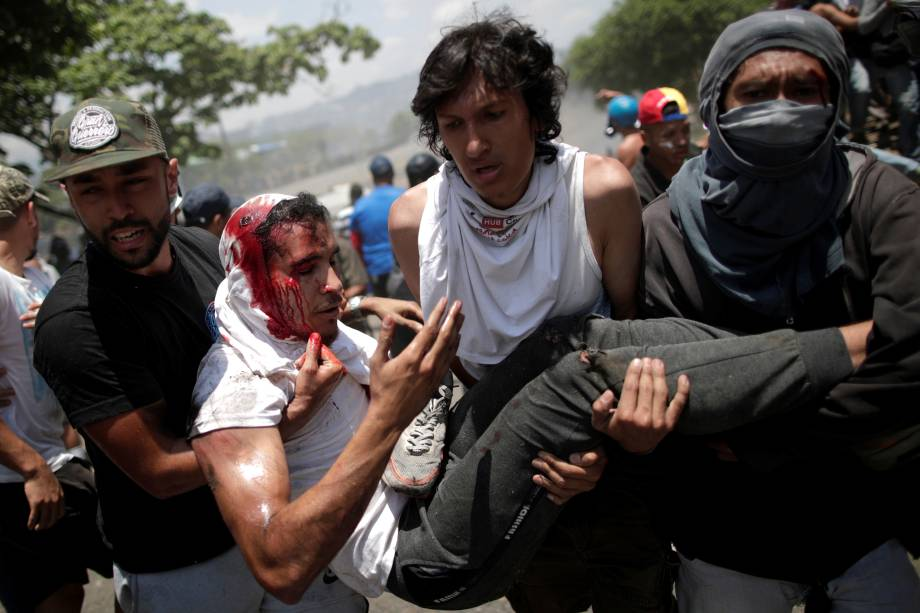 Manifestante ferido é carregado após ser atropelado por um veículo da Guarda Nacional Bolivariana nos arredores da base aérea La Carlota em Caracas, na Venezuela - 30/04/2019
