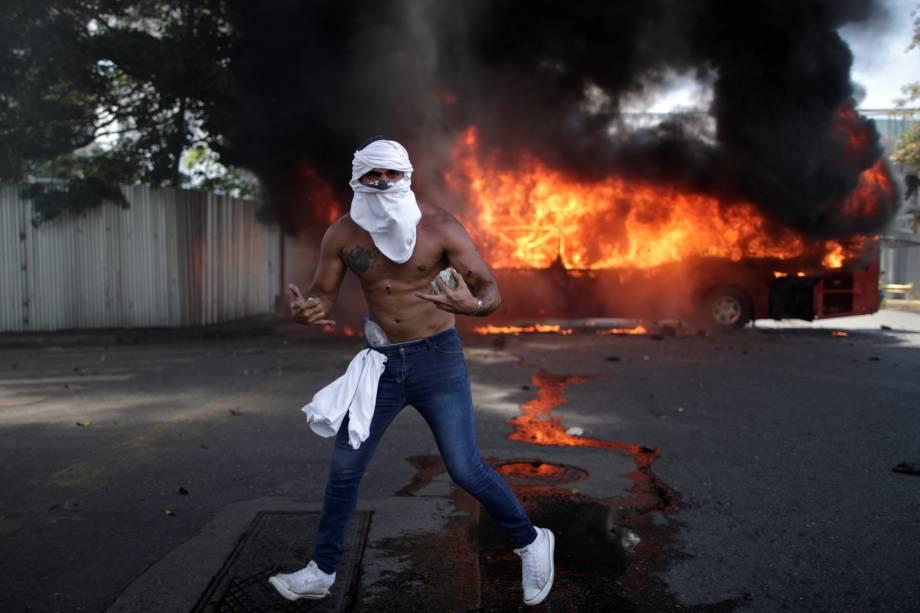 """Manifestante de oposição é visto com pedras na frente de ônibus incendiado, próximo da base aérea Generalisimo Francisco de Miranda  """"La Carlota""""em Caracas, capital da Venezuela - 30/04/2019"""