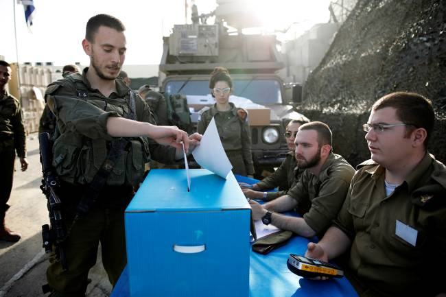 Soldado israelense deposita sua cédula de votação em urna seção eleitoral próxima da Faixa de Gaza – 07/04/2019