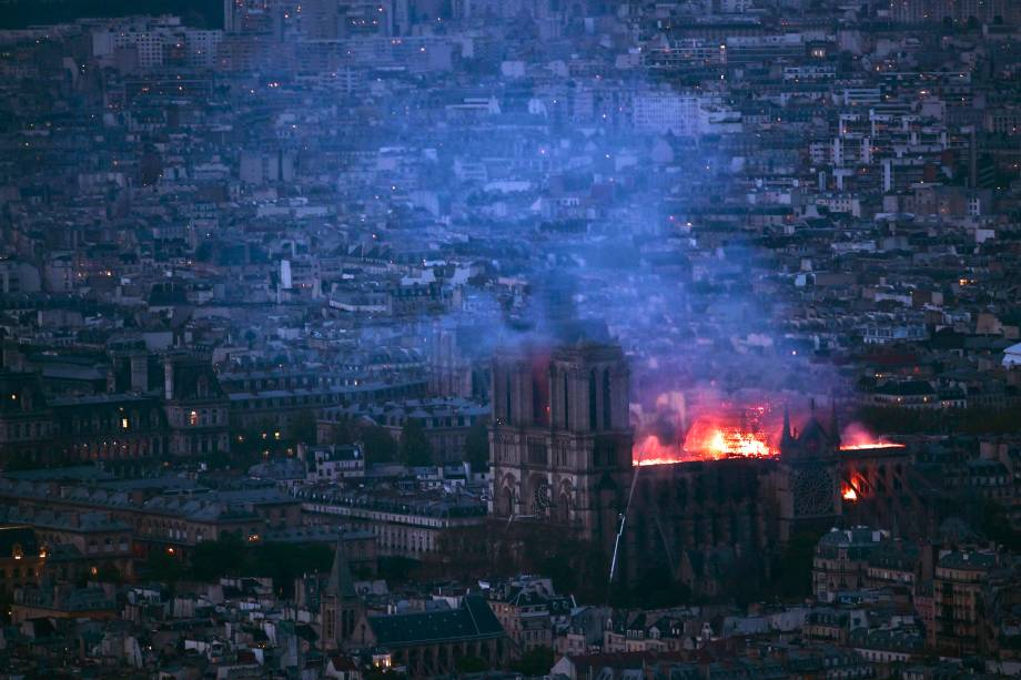 Vista geral da Torre Montparnasse mostra chamas e fumaça sobre o teto da Catedral de Notre-Dame, em Paris - 15/04/2019