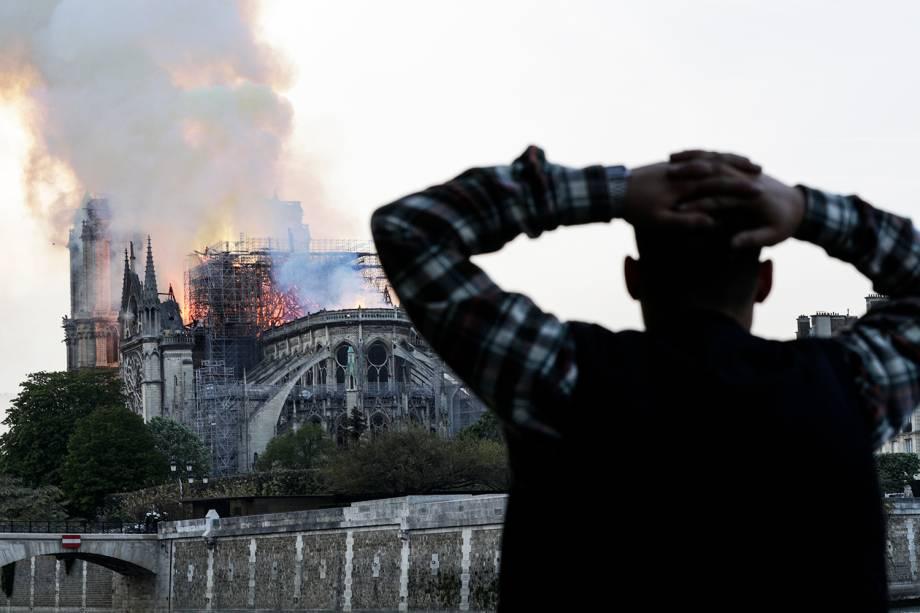 Homem observa incêndio atingir o topo da Catedral de Notre-Dame, localizada na região central de Paris, França - 15/04/2019