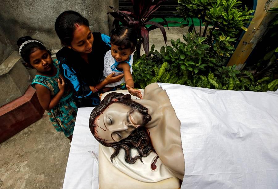 Mulher ajuda a filha a tocar uma imagem de Jesus Cristo depois de participar de uma oração da Sexta-Feira Santa em Calcutá, Índia - 19/04/2019