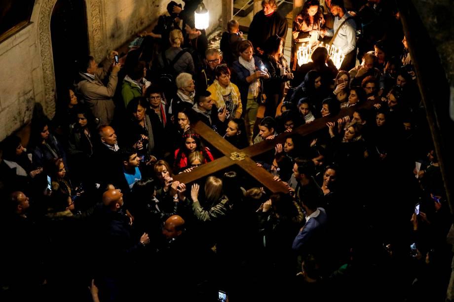 Fiéis cristãos carregam uma cruz de madeira para a Igreja do Santo Sepulcro durante a procissão da Sexta-Feira Santa ao longo da Via Dolorosa na Cidade Velha de Jerusalém - 19/04/2019