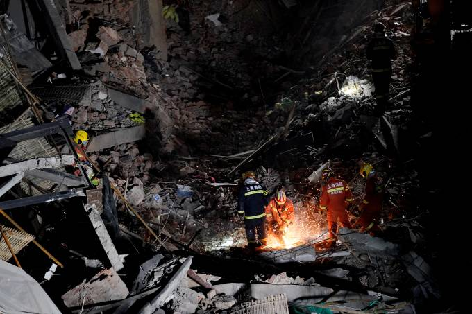 Firefighters work at the site where a building collapsed, in Shanghai