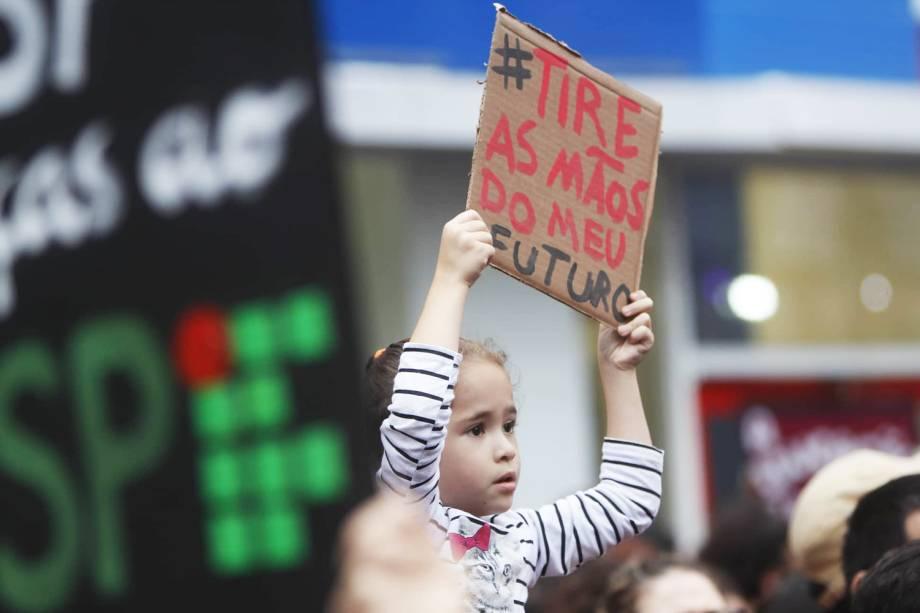 """Criança exibe placa com os dizeres """"Tire as mãos do meu futuro"""" , durante protesto contra os cortes na área da educação e pesquisa anunciados pelo Governo Federal, na avenida Paulista, em São Paulo (SP) - 15/05/2019"""