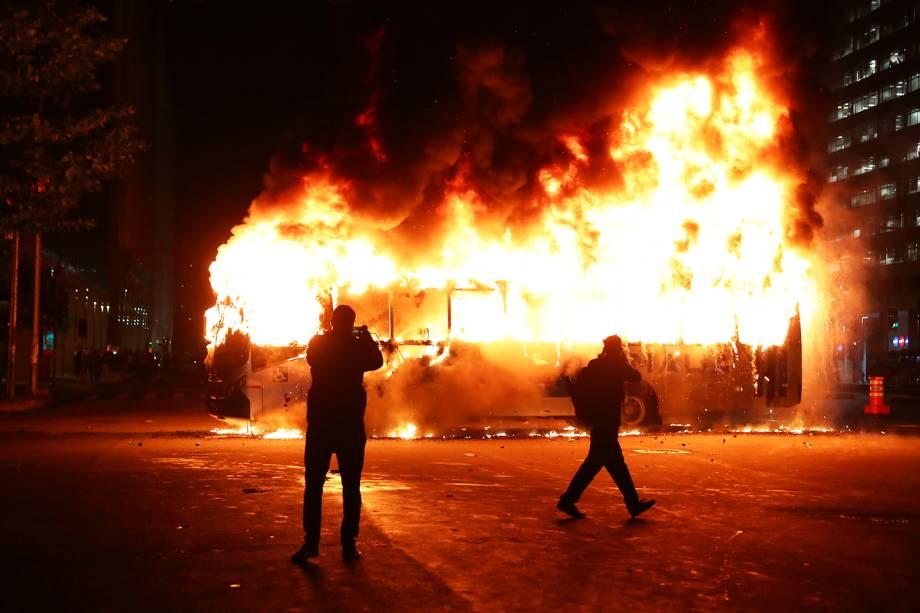 Pessoas tiram fotos de ônibus incendiado durante protesto contra o corte de verba nas universidades federais, no Rio de Janeiro (RJ) - 15/05/2019