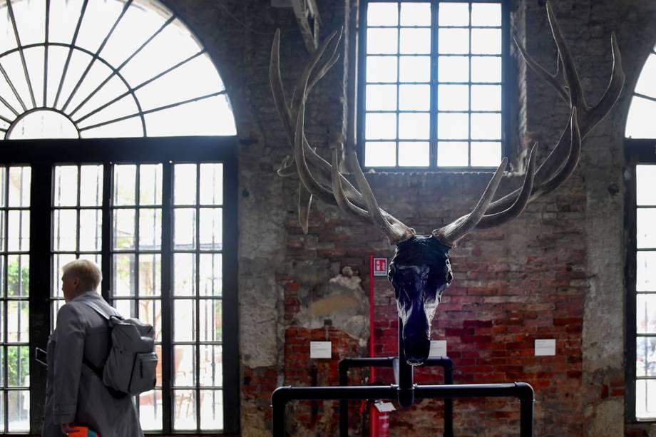 """Visitante passa por uma obra do escultor americano Jimmie Durham, durante a 58ª Bienal Internacional de Arte de Veneza, na Itália. A exposição tem como tema """"May You Live in Interesting Times"""""""