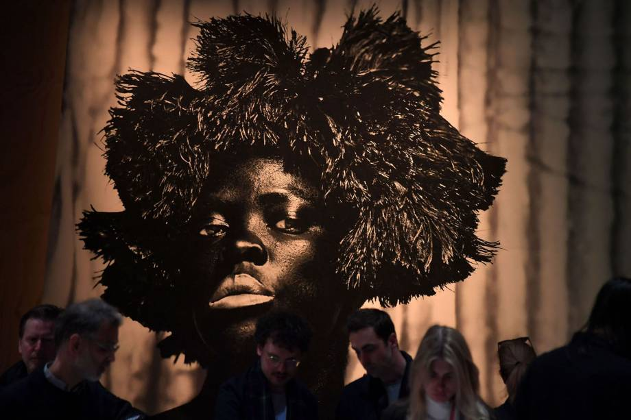 """Visitantes observam obra da artista sul-africana Zanele Muholi, durante coletiva de imprensa, antes da abertura oficial da  58ª Bienal Internacional de Arte de Veneza, na Itália. A exposição tem como tema """"May You Live in Interesting Times"""""""