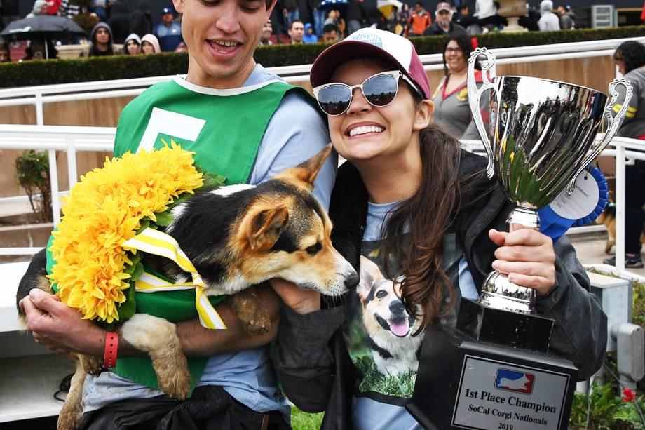 """Bradley Taylor e Jessica Wick carregam o cão Emmett e o troféu de campeão após a segunda edição do """"Corgi Nationals"""" - competição realizada na cidade de Arcadia, localizada no estado americano da Califórnia - 26/05/2019"""