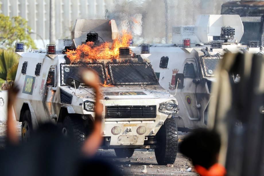 Manifestantes colocam fogo em veículo militar durante confronto em Caracas, capital da Venezuela - 01/05/2019