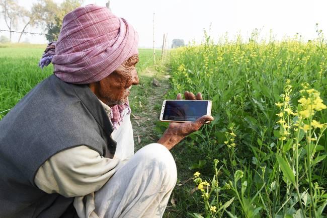 Fazendeiro indiano assiste discurso do político em seu celular, no vilarejo de Majadia – 01/02/2019
