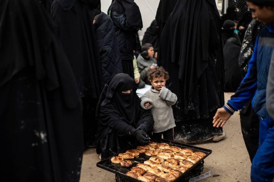Mulher e criança aguardam a vez para comerem pão no no campo de Al-Hol, que abriga membros do autoproclamado Estado Islâmico (ISIS), no nordeste da Síria