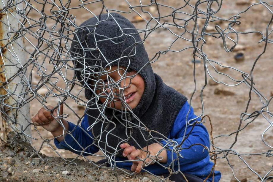 Menino brinca com cerca de arame que fecha o acampamento Al-Hol