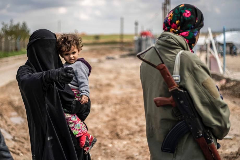 Mulheres andam armadas dentro do acampamento sírio