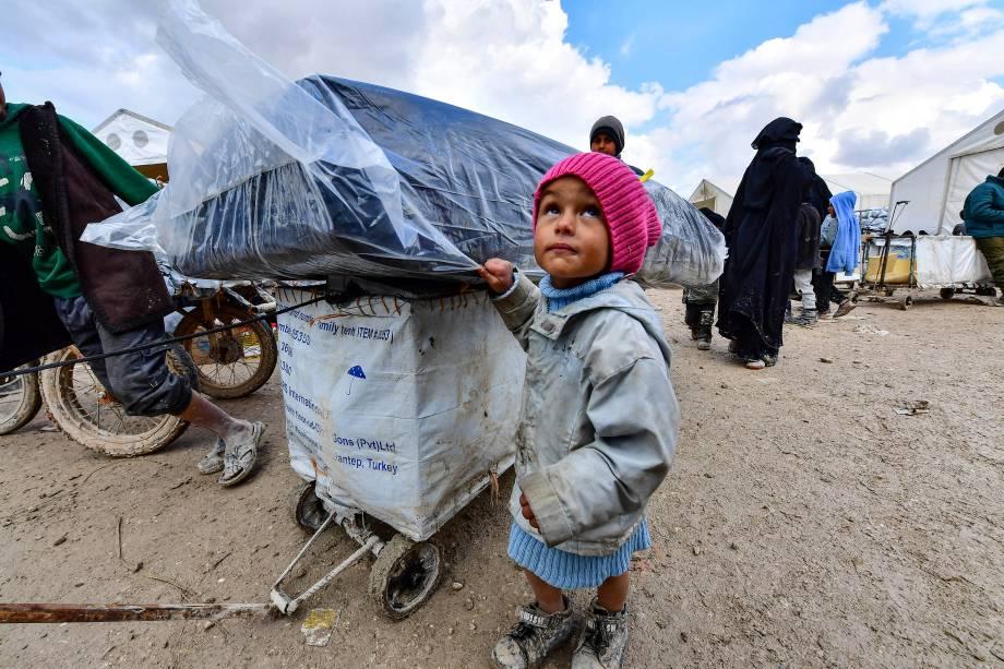 Criança espera montagem de barraca em Al-Hol