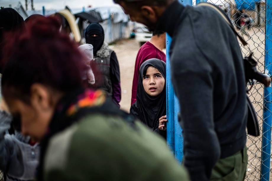 Membro das Forças Democráticas da Síria (SDF) abre porta para uma menina no campo de Al-Hol