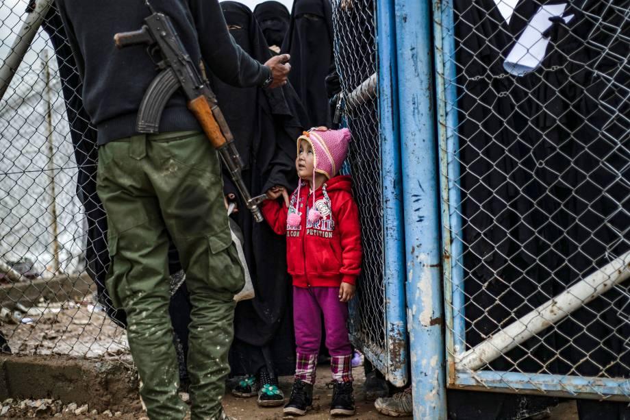 Menina olha para membro das Forças Democráticas da Síria (SDF) no campo de al-Hol, que abriga parentes de membros do grupo Estado Islâmico (IS), na província de al-Hasakeh, nordeste da Síria - 28/03/2019