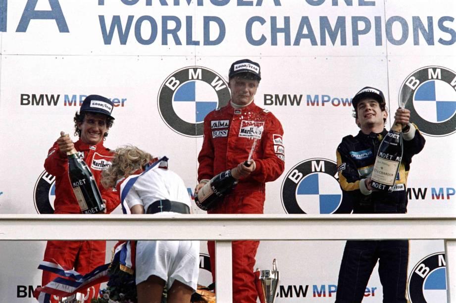 NikI Lauda, da McLaren, comemora a vitória no Grande Prêmio da Holanda de 1985, no pódio com o francês Alain Prost, também da McLaren, e o brasileiro Ayrton Senna, da Lotus