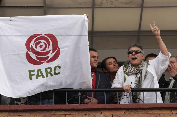 Former commander of Colombia's Marxist FARC Jesus Santrich greets people from the balcony  of FARC's headquarters in Bogota