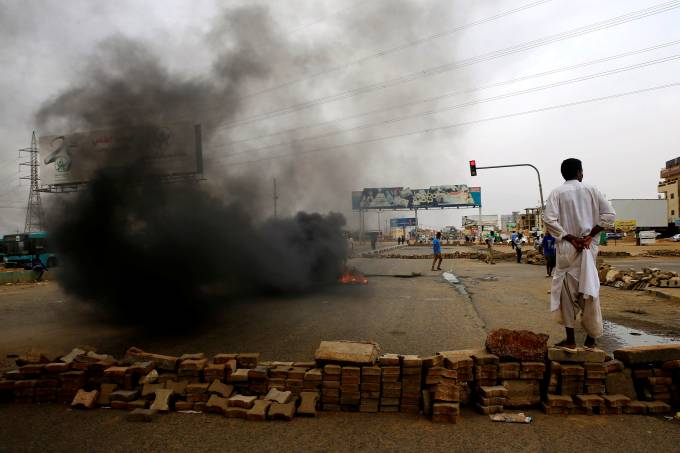 A Sudanese protester stands near a barricade on a street, demanding that the country's Transitional Military Council handover power to civilians, in Khartoum