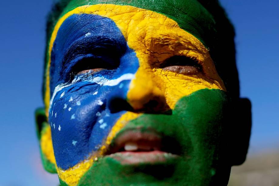 Maanifestante pinta rosto com as cores da bandeira brasileira durante protesto realizado em Brasília (DF) a favor do ministro Sergio Moro e da Operação Lava-Jato - 30/06/2019