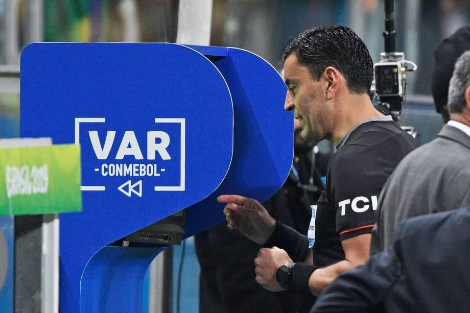 O árbitro chileno Roberto Tobar Vargas checa o VAR durante partida entre Brasil e Paraguai - 27/06/2019