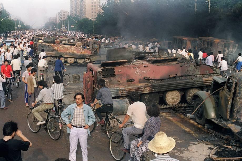 Chineses se reúnem perto dos restos mortais de mais de 20 veículos blindados queimados por manifestantes durante confrontos com soldados perto da Praça Tiananmen, em Pequim - 04/06/1989