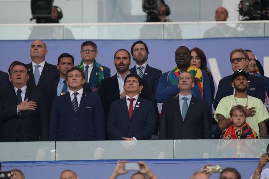 O presidente Jair Bolsonaro (o primeiro da esq. para dir.) e Neymar (o último) põem a mão no peito durante a execução do hino nacional brasileiro no estádio do Maracanã