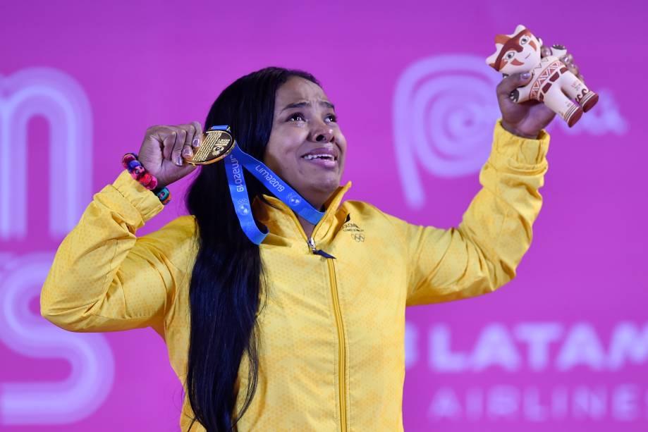 Mercedes Perez, da Colômbia, se emociona no pódio ao conquistar a medalha de ouro no Levantamento de Peso, na categoria até 64kg