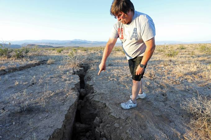 A man looks into a fissure that opened in the desert during a powerful earthquake that struck Southern California, near the city of Ridgecrest