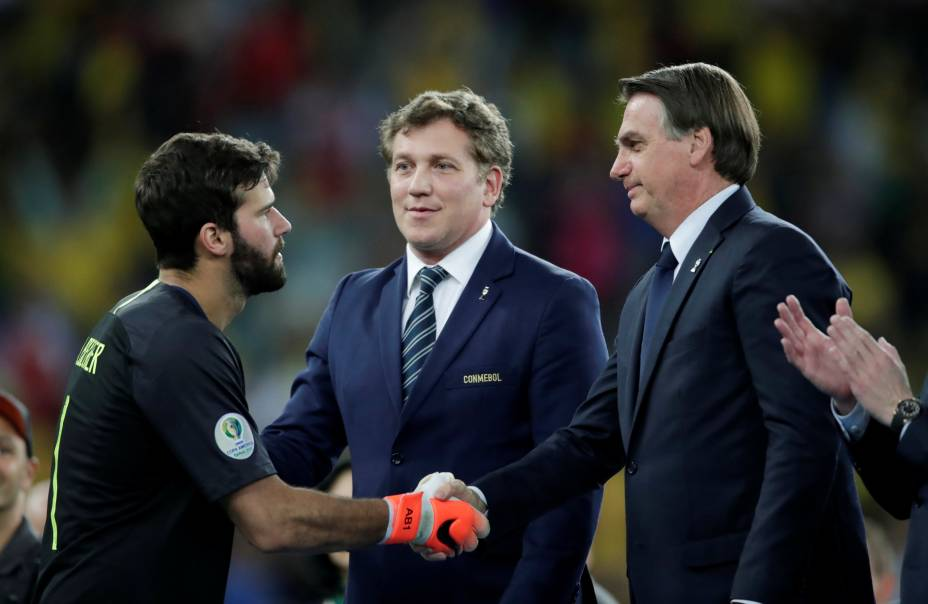 O goleiro Alisson, Alejandro Domínguez, presidente da Conmebol, e o presidente Jair Bolsonaro