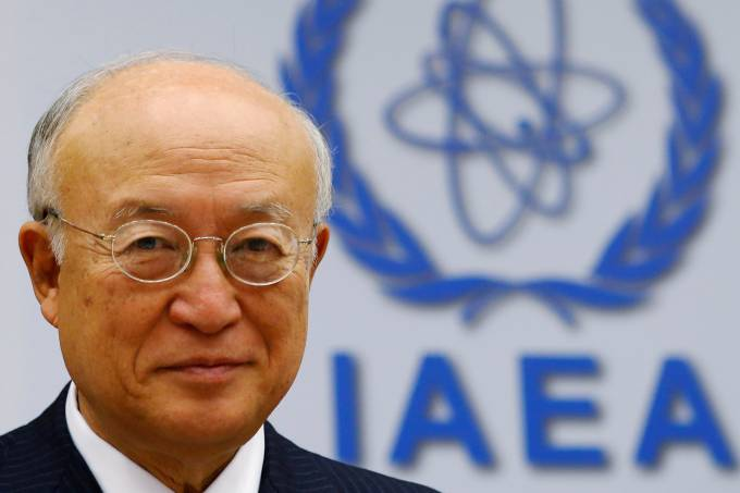 FILE PHOTO: IAEA Director General Amano smiles as he waits for a board of governors meeting to begin at the IAEA headquarters in Vienna
