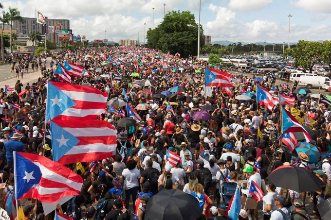 People gather along a main highway during a protest calling for the resignation of Governor Ricardo Rossello in San Juan