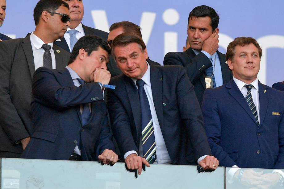 O ministro da Justiça Sergio Moro conversa com o presidente Jair Bolsonaro na tribuna de honra do estádio do Maracanã