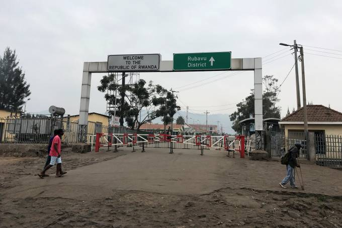 Congolese people walk near the gate barriers at the border crossing point with Rwanda following its closure over Ebola threat in Goma