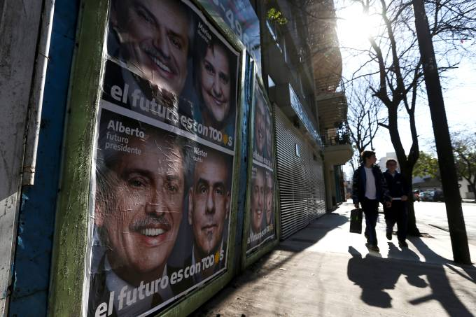 Pedestrians walk by a poster for Alberto Fernandez in Buenos Aires
