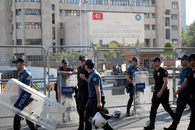 Turkish police walk in front of the Metropolitan Municipality headquarters in Diyarbakir