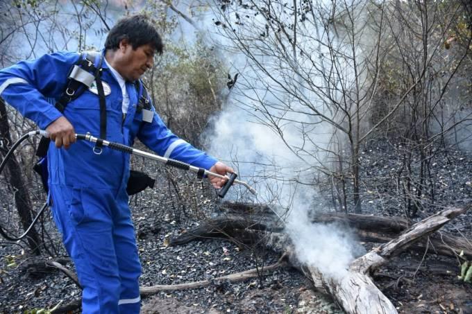 Bolivia's President Evo Morales sprays water in the burned forest in Santa Rosa