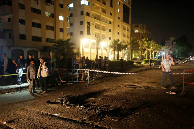 Palestinians check the scene following an explosion in Gaza City
