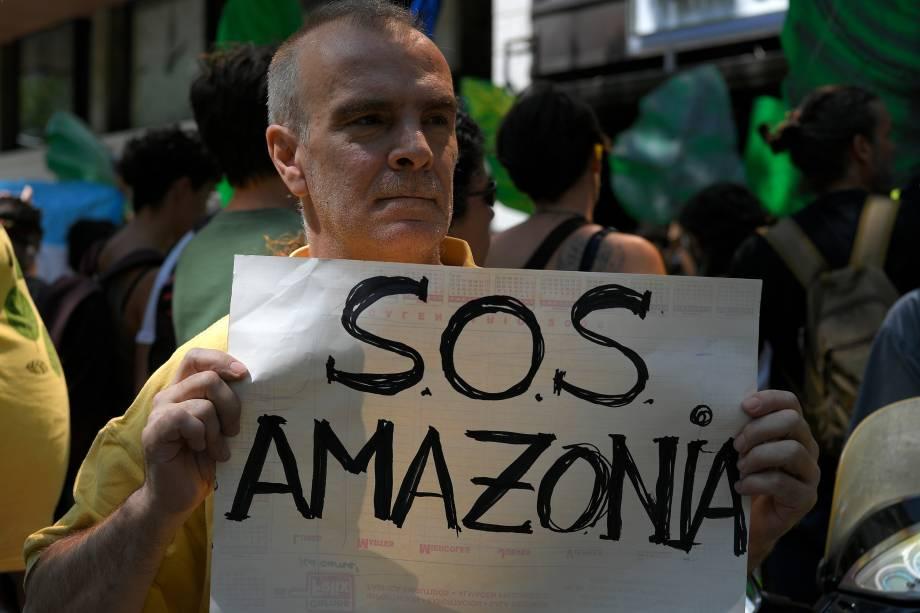"""Um ativista climático segura uma placa com a inscrição """"SOS Amazon"""" durante uma manifestação em Barcelona, na Espanha"""