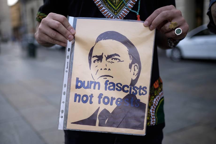 """Um manifestante segura um cartaz com a inscrição """"Queime fascistas, não florestas"""" durante uma manifestação na Piazza Castello, em Turim, na Itália"""