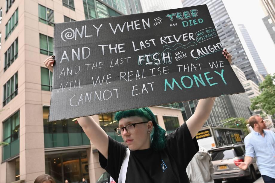 Ativista levanta uma placa de protesto em frente ao Consulado Geral do Brasil, Nova York, nos EUA