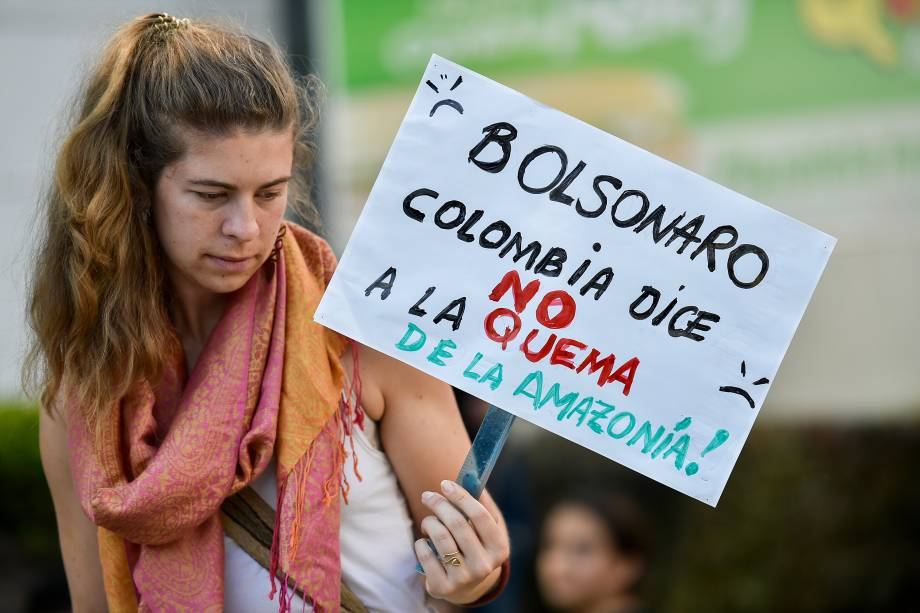 """Um ativista da mudança climática segura uma placa com a inscrição """"Bolsonaro, a Colômbia diz NÃO à queima da Amazônia"""", durante um protesto em frente ao consulado brasileiro em Cali, Colômbia"""