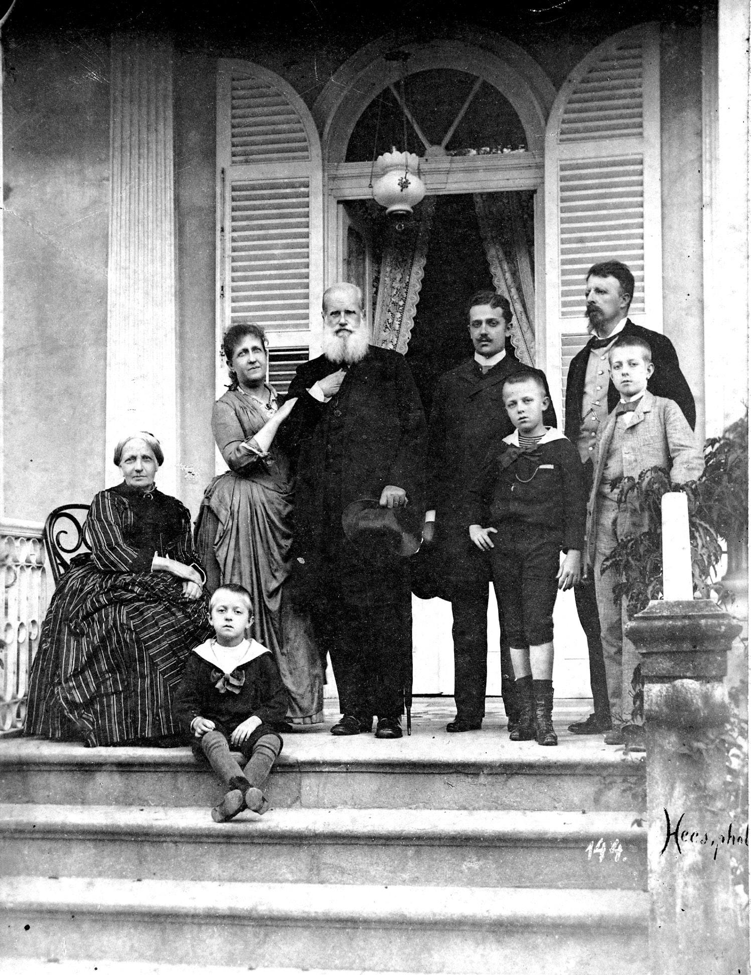 A Família Imperial na varanda da residência da princesa Isabel e do conde d'Eu, em Petrópolis, hoje Casa da Princesa. Da esquerda para a direita: d. Teresa Cristina, sentada, a princesa Isabel, de braços dados com d. Pedro II, d. Pedro Augusto e o conde d'Eu, todos em pé. Na frente, d. Luís e d. Pedro, príncipe do Grão-Pará. No degrau da escada, d. Antônio, sentado, aos pés de sua avó. Circa 1889