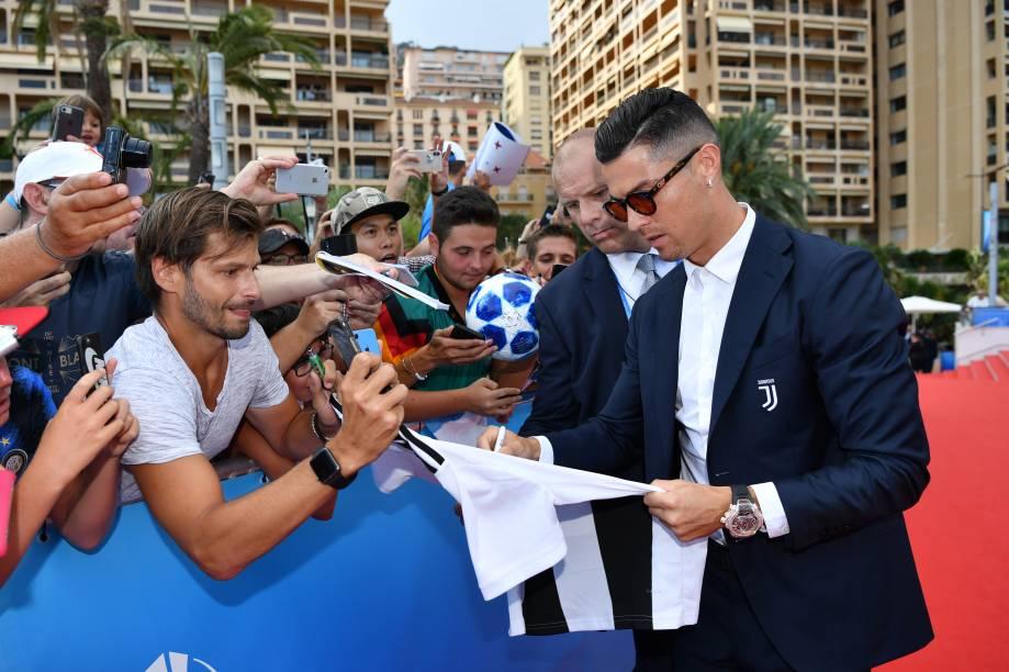 Cristiano Ronaldo atende os fãs ao chegar na premiação da Uefa em Mônaco