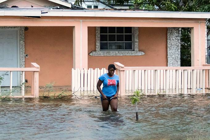 A woman walks in a flooded street after the effects of Hurricane Dorian arrived in Nassau